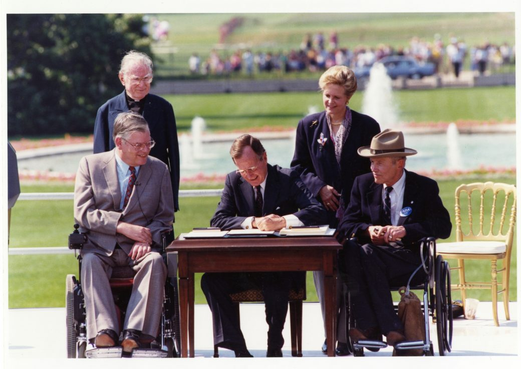 Signing of the ADA by George H.W. Bush with onlookers outside