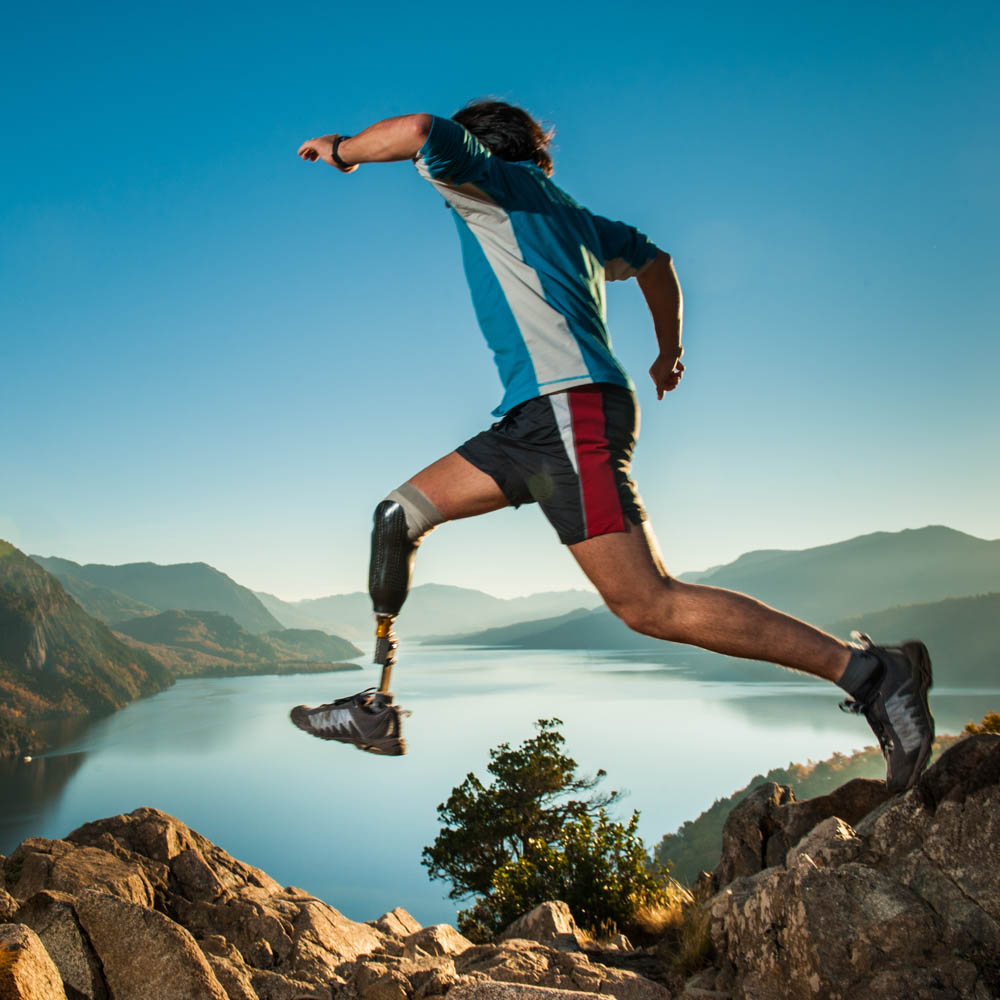 disabled runner leaping with lake in background