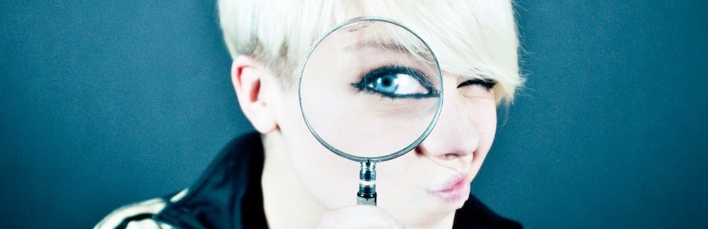 Woman with magnifying glass - metaphor for website google analytics & adwords auditing